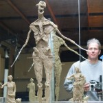Artist with concept models and maquette armature for Pioneer Woman